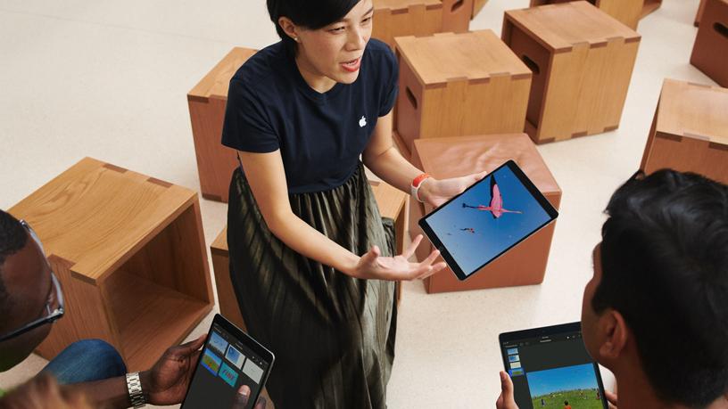 一名 Apple 团队成员和两名顾客正在使用 iPad。