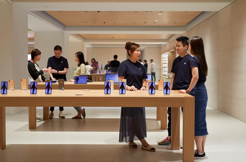 Apple 员工站在 Apple Marunouchi 中的 iPhone 展示桌旁。