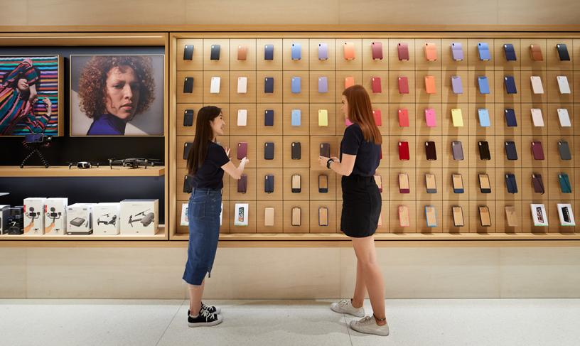 人们站在陈列着多种 iPhone 保护壳的展示墙前。