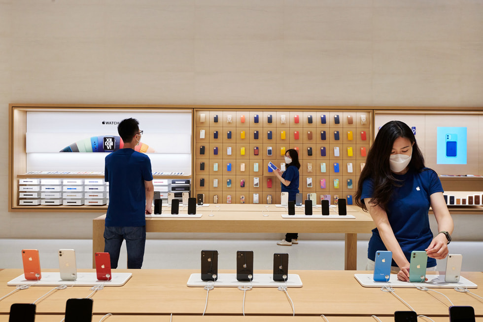 Apple 长沙零售店内,零售团队成员正在设置产品展示桌上的 Apple 设备。
