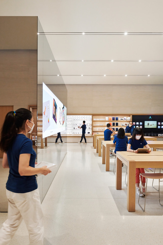 Apple 长沙零售店内,店员站在产品展示桌和独立式 video wall 影像墙旁。