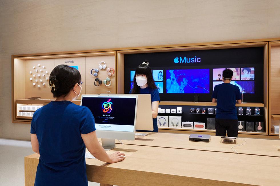 在 Apple 长沙零售店内,店员正在产品展示桌旁使用 iMac。