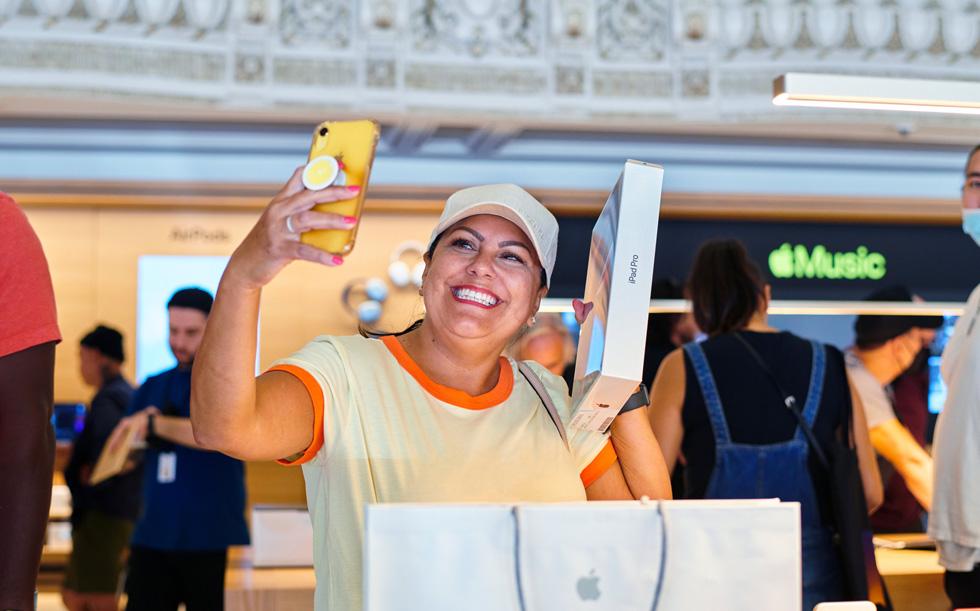 一名顾客在 Apple Tower Theatre 自拍照片,庆祝自己购买了新 iPad Pro。