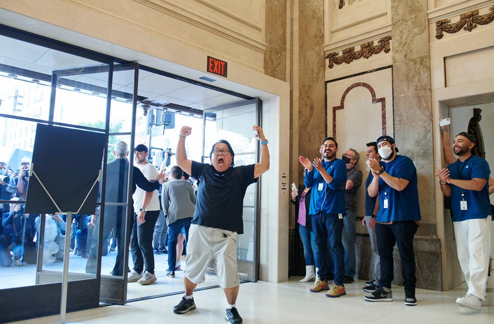一位顾客在走进 Apple Tower Theatre 时,举起手臂以示庆祝。
