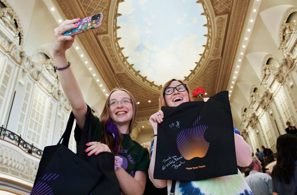 顾客在 Apple Tower Theatre 绘有天空图案的穹顶下与他们购买的 Apple 产品自拍合影。