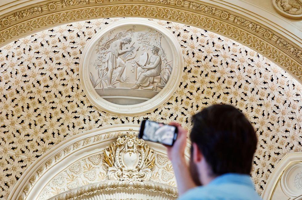 一名顾客使用 iPhone 拍摄 Apple Tower Theatre 的装饰细节。