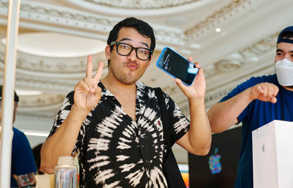 一名顾客在 Apple Tower Theatre 中一手举着和平标牌,另一手拿着 iPhone 12。