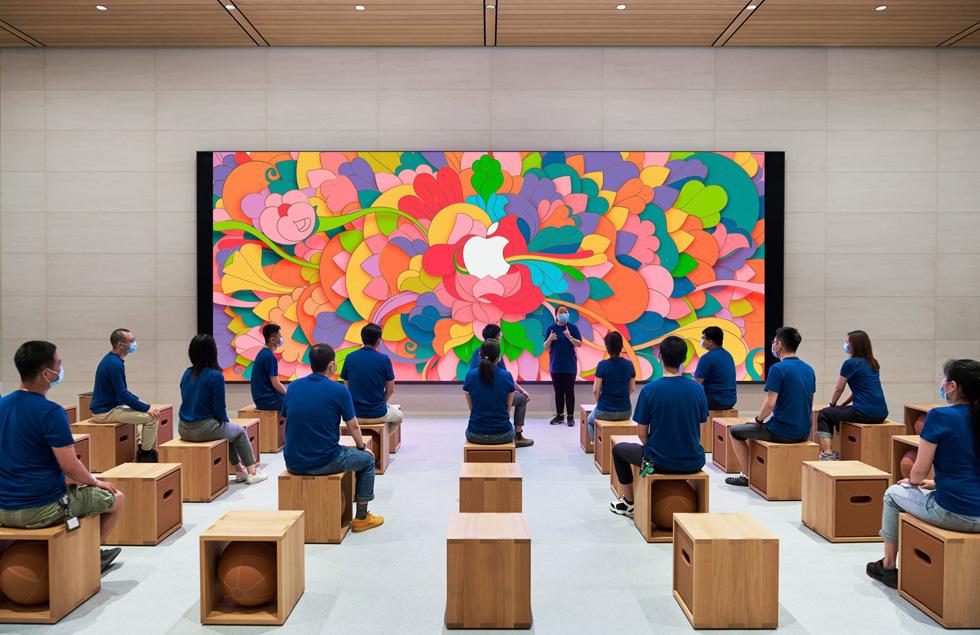 几位身穿蓝色上衣、佩戴口罩的 Apple 员工坐在 Forum 互动坊内聆听演讲,每个人都注意保持社交距离。