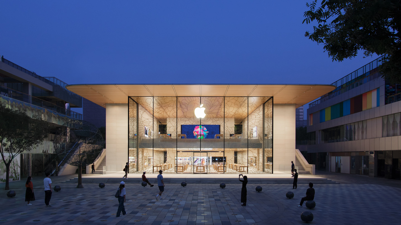 傍晚时分的 Apple 三里屯店面外景,展现灯火通明的店内,突显建筑物设计的通透感和流动性。