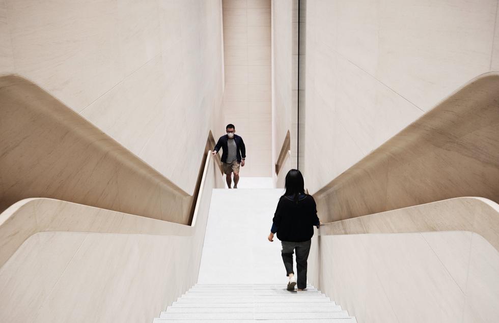 两位访客在店内的其中一侧楼梯上,一位戴着口罩往上走,另一位往下走。