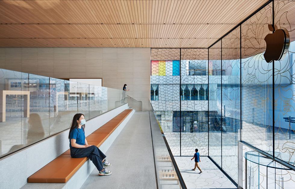 一位 Apple 员工佩戴口罩坐在上层 Viewing Gallery 景廊内的长椅上,望向外面的广场。