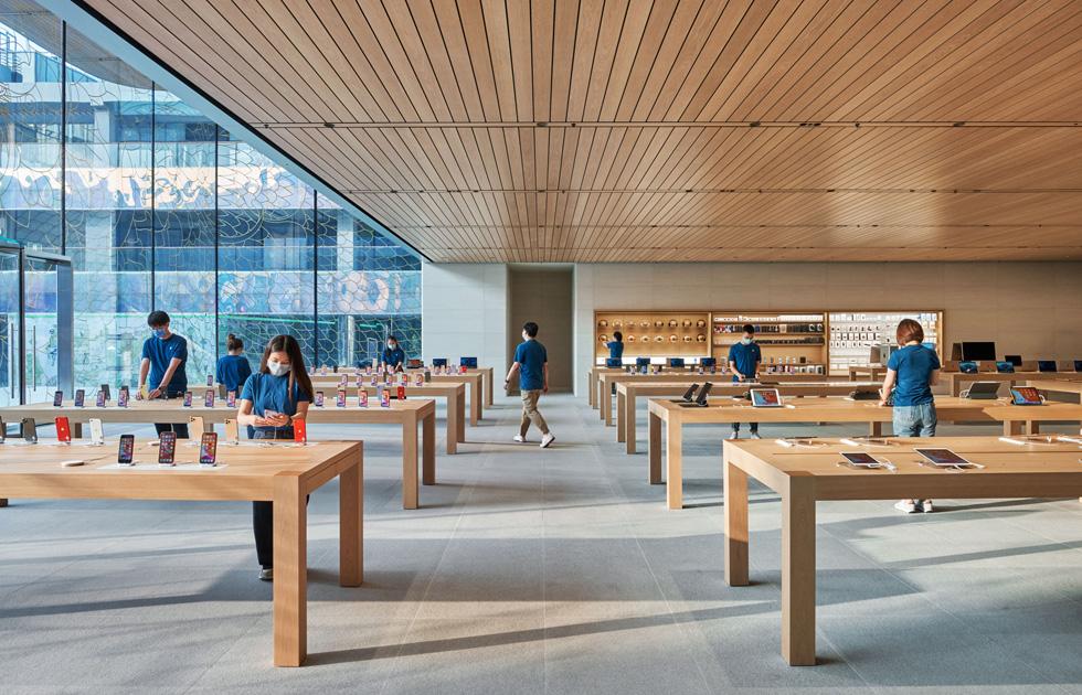 Apple 员工位于产品展示台前。