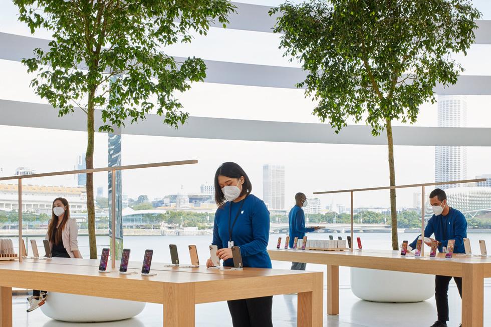 一名 Apple 工作人员将 iPhone 放在展示架上。