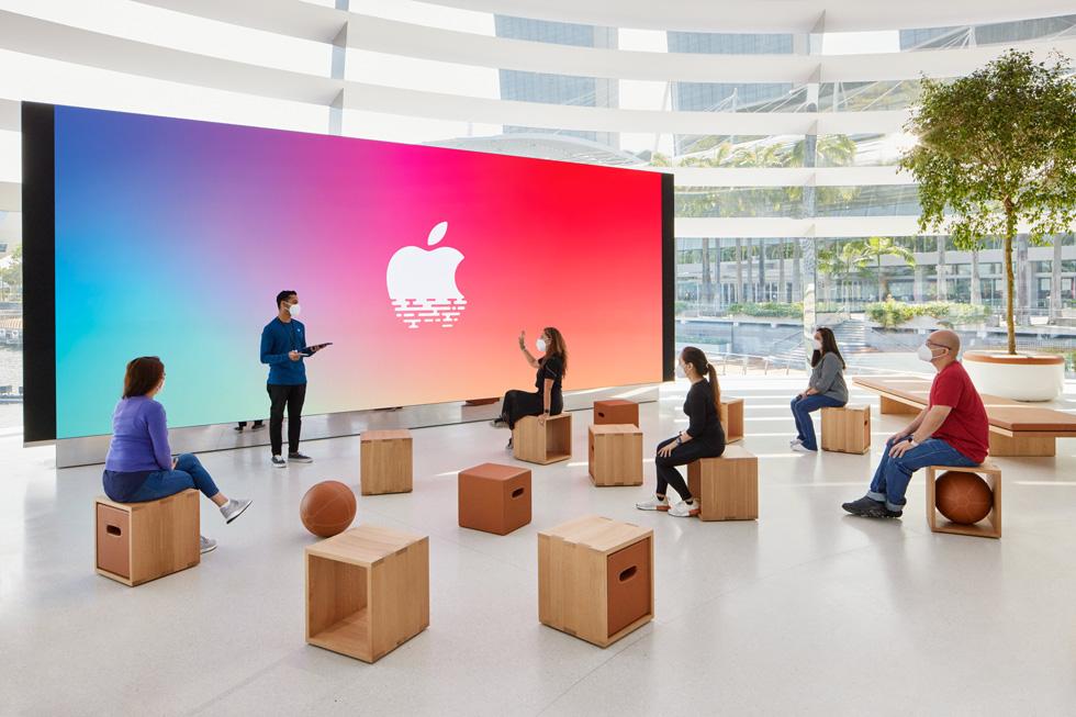 顾客坐下来聆听 Apple 工作人员的讲解。