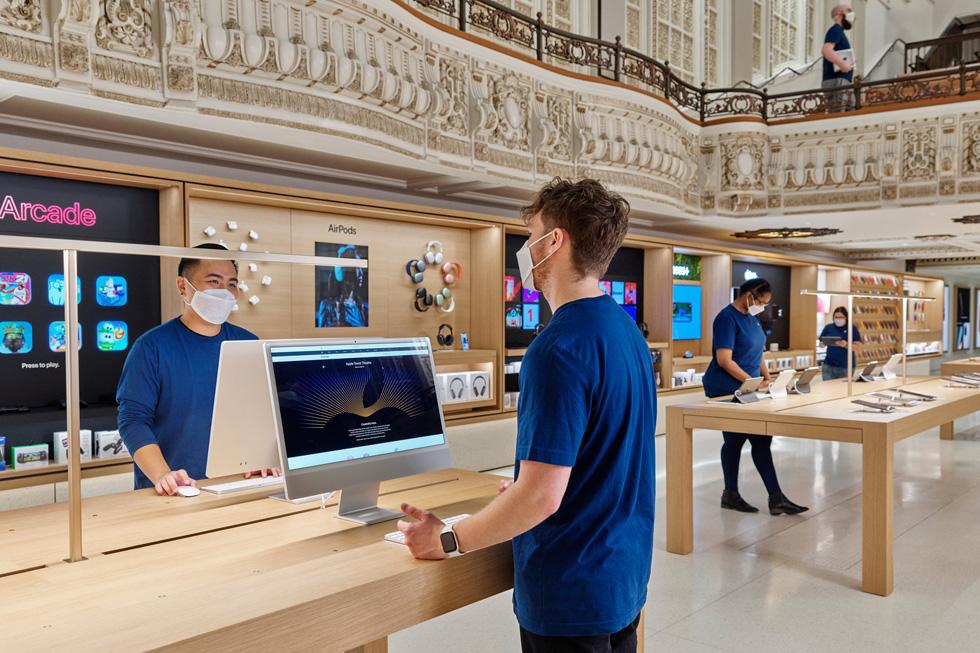 Apple Tower Theatre 团队成员在 iMac 与 iPad 展示桌旁。