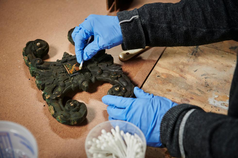 一块装饰性铜金属片被小心地重新安放在原有的饰面上。