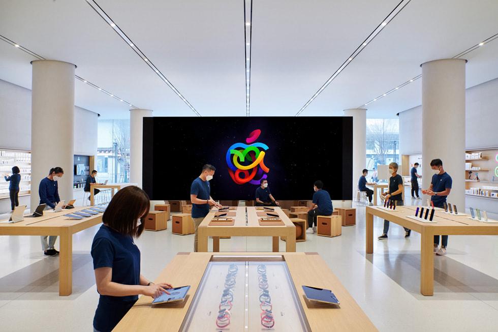 Apple 长沙零售店内,独立式 video wall 影像墙面向产品展示桌,Apple Specialist 专家站在产品展示桌旁。