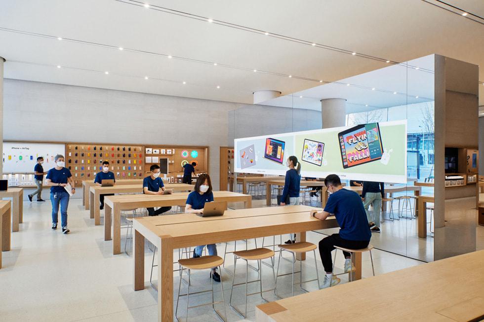 在 Apple 长沙零售店内,顾客们站在产品展示桌与独立式 video wall 影像墙旁。