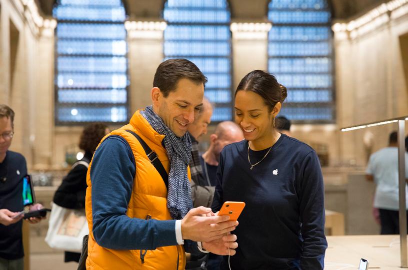 Apple Grand Central 的一名店员正在协助顾客熟悉 iPhone XR。
