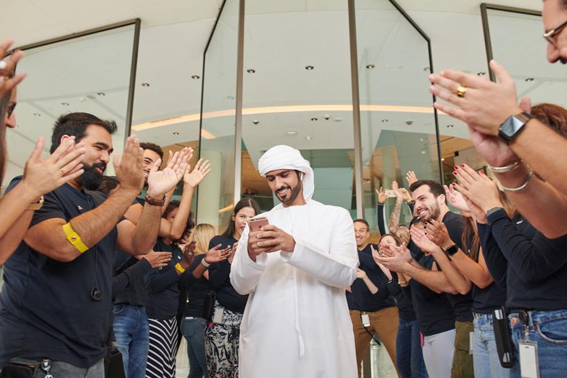 顾客周围围绕着正在鼓掌的 Apple 团队成员。