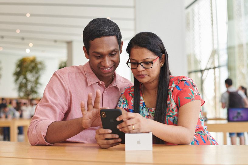 一位男性顾客和一位女性顾客正在体验 iPhone Xs Max。