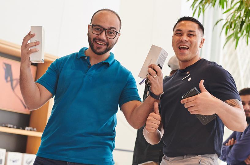 顾客手持两个 iPhone Xs 包装盒与 Apple 团队成员合影。