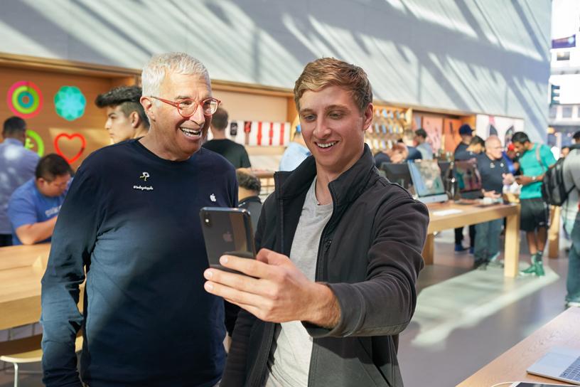 位苹果员工看着顾客用 iPhone Xs 自拍。