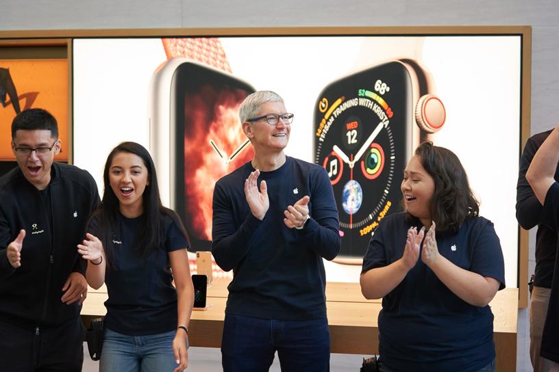 一位顾客拿着 Apple Watch Series 4 和 iPhone Xs 的盒子与一位苹果员工合照。