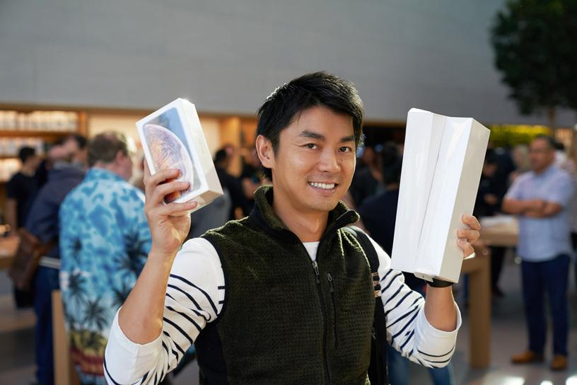 一位苹果员工看着顾客用 iPhone Xs 自拍。