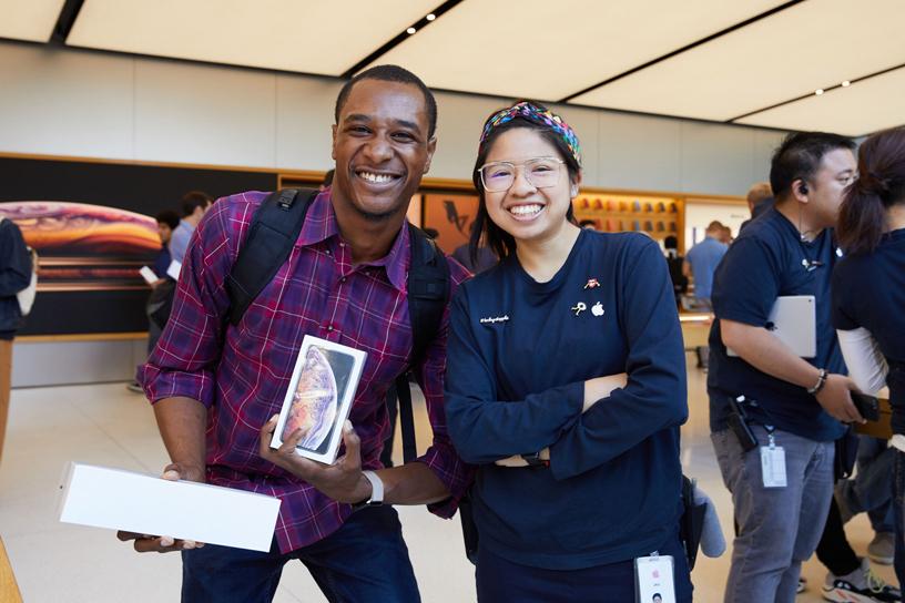 位顾客拿着 Apple Watch Series 4 和 iPhone Xs 的盒子与一位苹果员工合照。