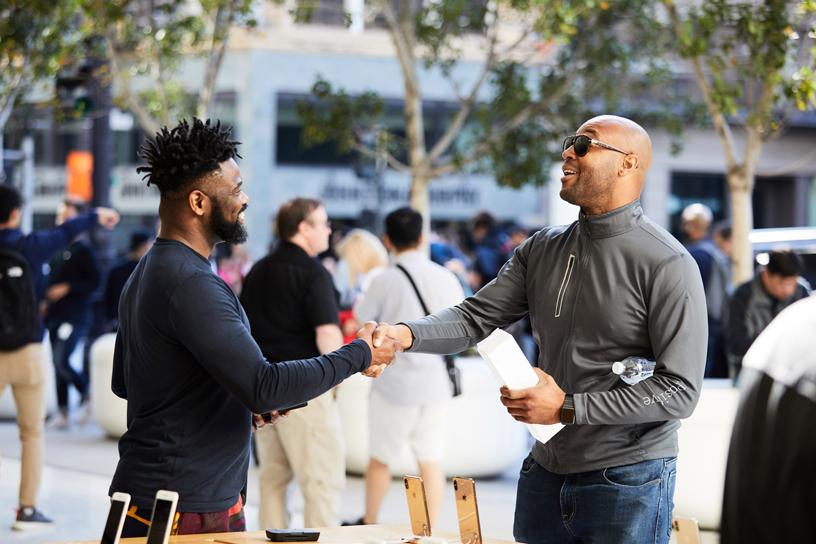 位苹果员工与顾客握手。