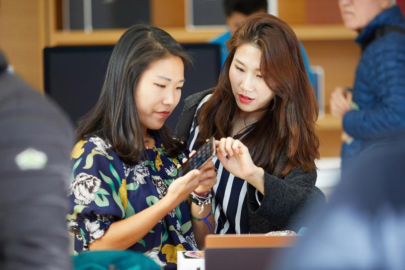 两位女士在研究手里的 iPhone Xs。