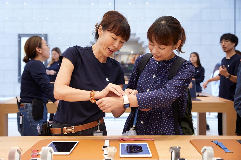 Apple 京都零售店内的团队成员正协助一位年轻女士体验 Apple Watch Series 4。