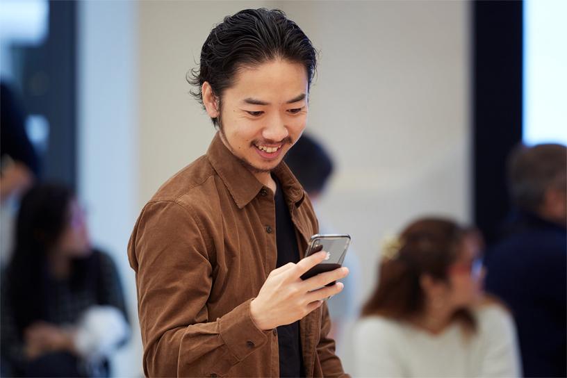 一位年轻的男士正在操作新款 iPhone Xs。