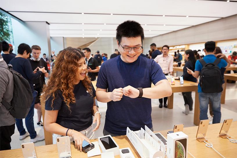 Apple 团队成员正协助一位顾客佩戴 Apple Watch Series 4。
