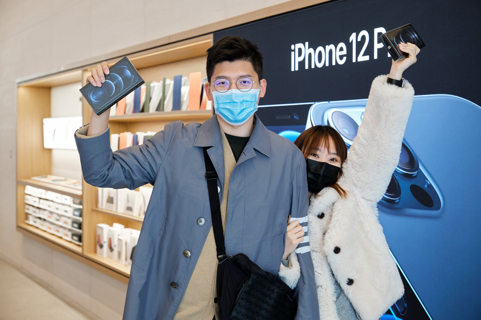 顾客在 Apple 三里屯零售店展示他们刚刚购买的全新 iPhone 12 Pro Max。
