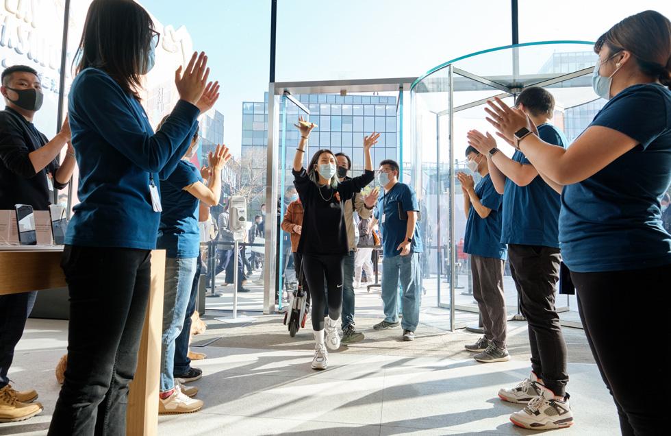 Apple 三里屯零售店的员工欢迎顾客前来了解新到货的 iPhone 12 Pro Max 和 iPhone 12 mini。