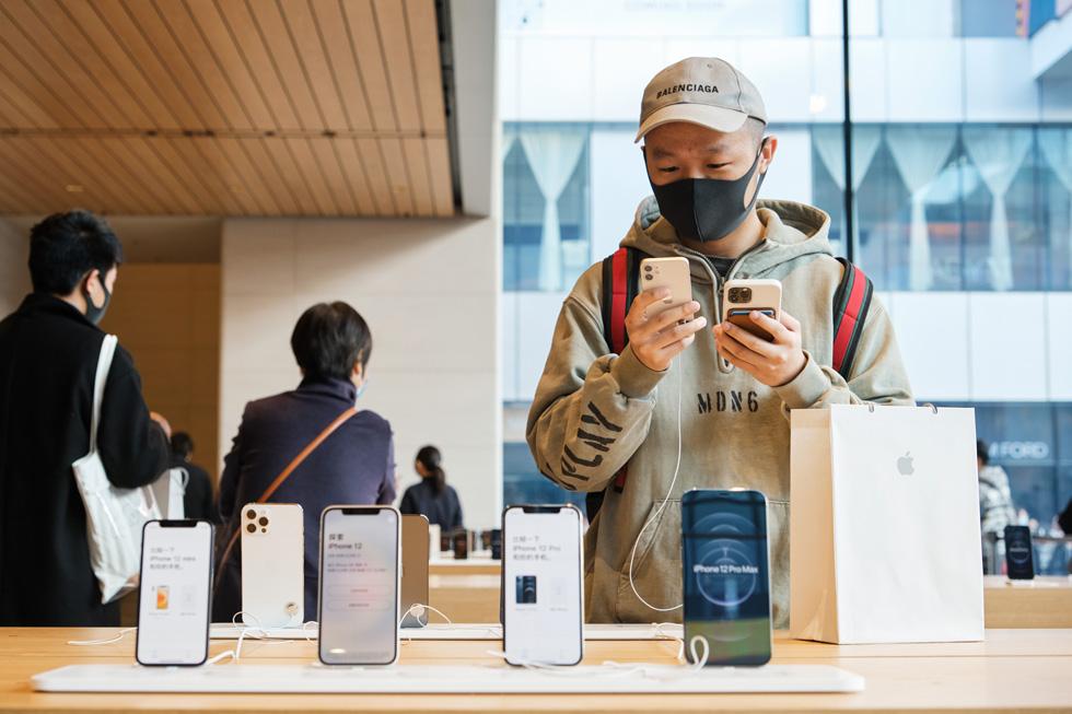 一位顾客在 Apple 三里屯零售店仔细查看 iPhone 12 mini。