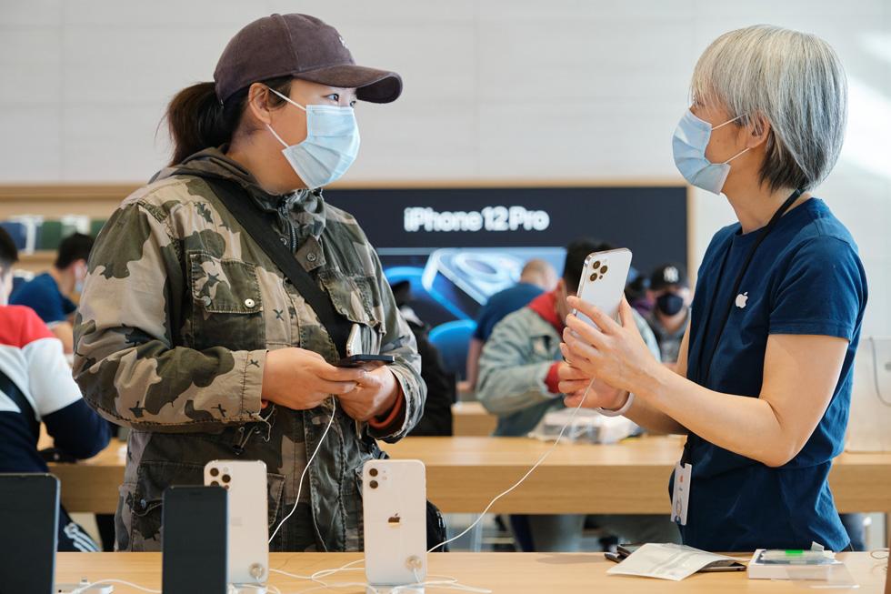 一位 Apple 三里屯零售店员工回答顾客有关 iPhone 12 Pro Max 的问题。
