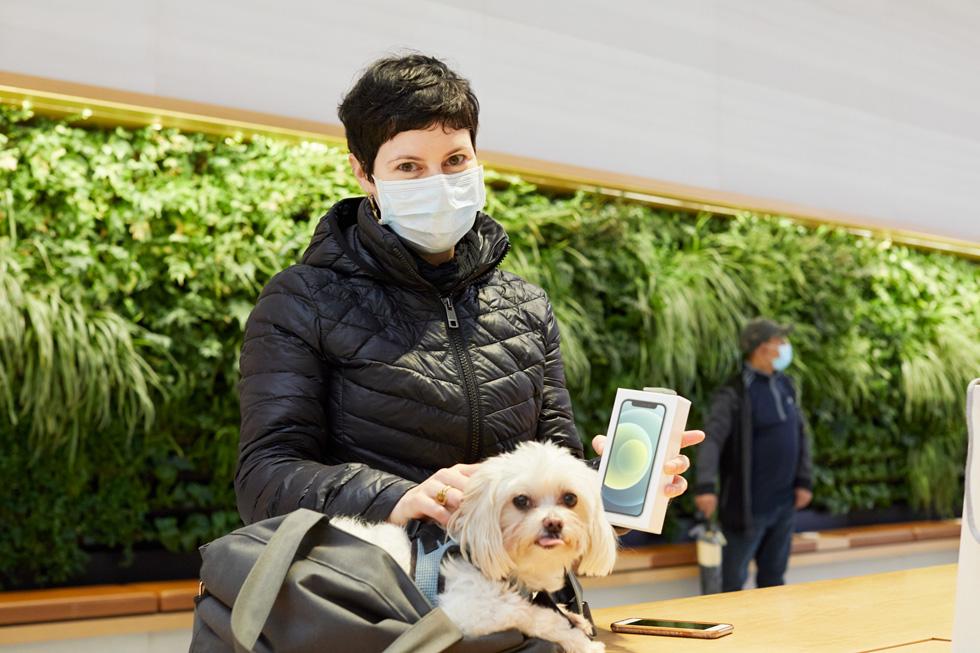 一位携带爱犬的顾客手持她的全新 iPhone 12 mini。