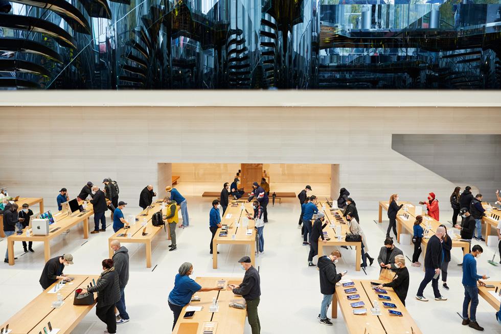 顾客和 Apple 员工围在 Apple 第五大道零售店的展示桌四周。
