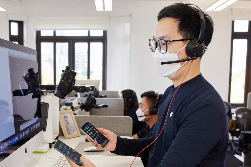 一位 Apple 在线团队成员在上海呼叫中心为顾客提供全新 iPhone 12 机型的咨询建议。