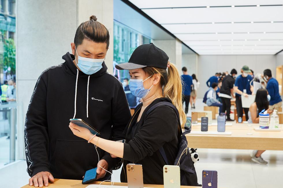 Apple Sydney 零售店的顾客在展示桌上试用全新 iPhone 12 Pro Max。