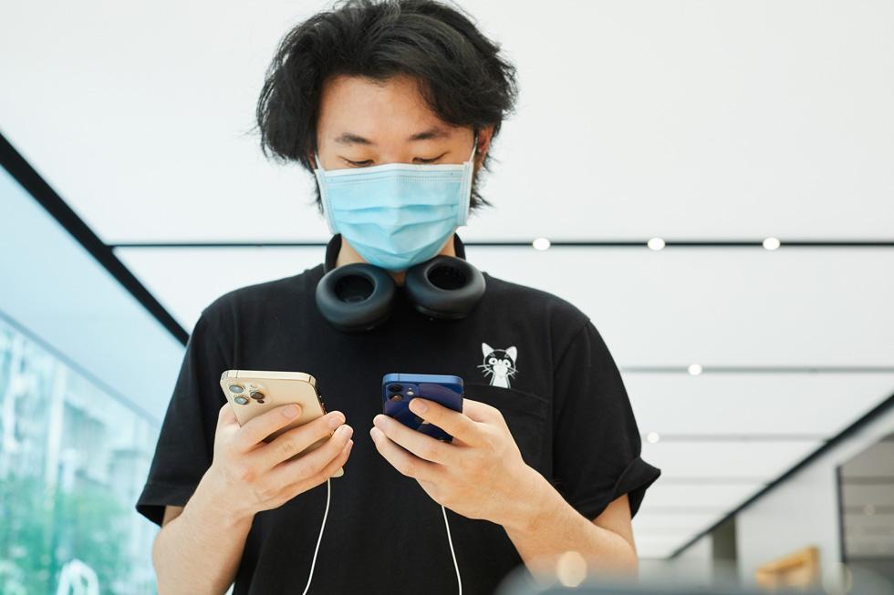 一位顾客正在 Apple Sydney 零售店对比 iPhone 12 Pro Max 和 iPhone 12 mini。