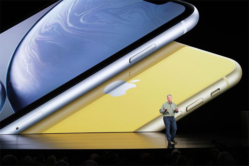 Phil Schiller 在以 iPhone XR 图片为背景的演讲台上。