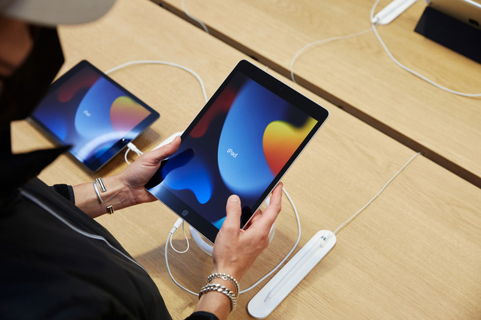 Apple Fifth Avenue 零售店内的顾客正在查看新款 iPad(第九代)。