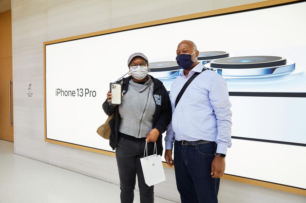 Apple Fifth Avenue 零售店的顾客正在展示与友人一同来购买的 iPhone 13 Pro。
