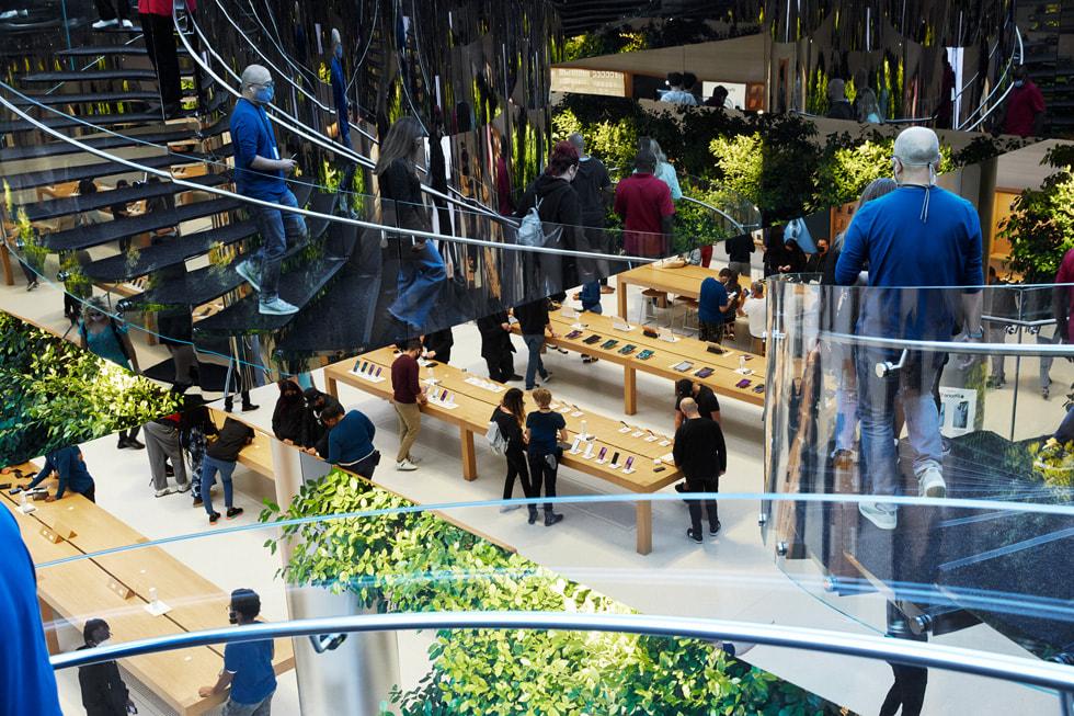 从楼梯上俯瞰 Apple Fifth Avenue 零售店内围绕着顾客与团队成员的展示台。