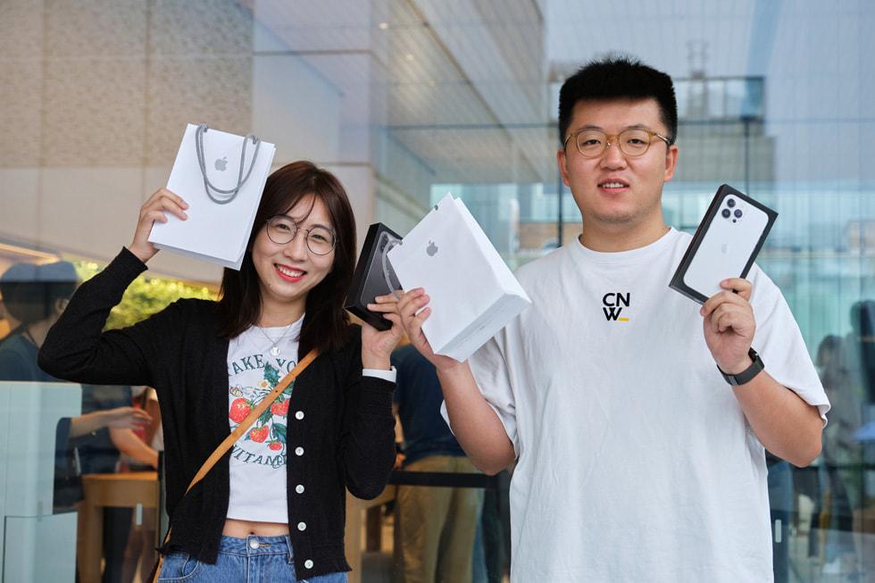 两名顾客正在庆祝自己购买到了 iPhone 13。