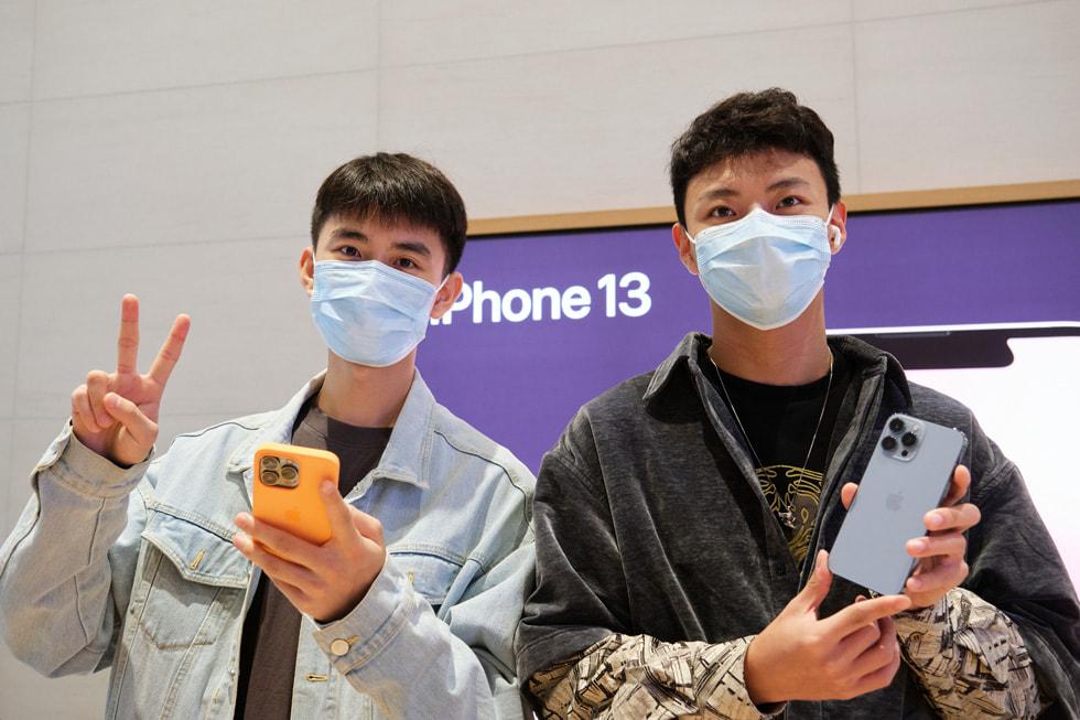 Apple 三里屯零售店内,一名与友人共同前来的顾客正在体验新款远峰蓝色 iPhone 13 Pro。